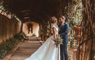 Novia con vestido de boda hecho a medida en corredor de flores