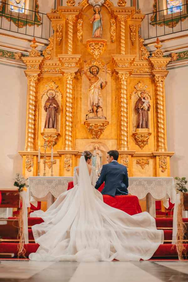 Novia con vestido de boda de cola larga en iglesia frente al altar