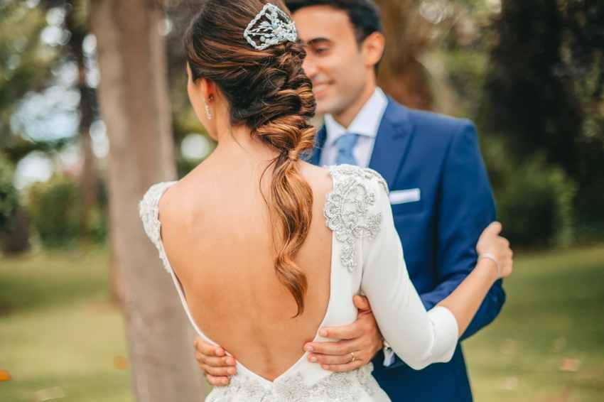 Novia de espaldas con vestido de boda hecho a medida con escote en esoalda